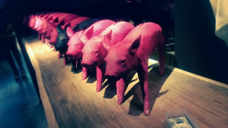 urban: Pink and black color piglet sculptures on table. Stock Photo