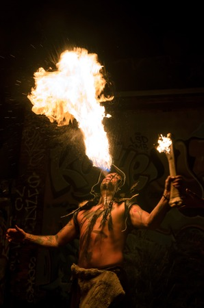 Men with tatoos costumed in shaman blowing   breathing fire Stock Photo