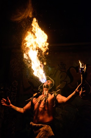 costumed: Men with tatoos costumed in shaman blowing   breathing fire Stock Photo