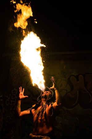 tatoos: Men with tatoos costumed in shaman blowing   breathing fire Stock Photo