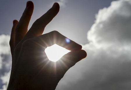 rule of thirds: OK hand with sun shining through Stock Photo