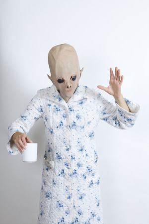 parody: Alien difficult to wake in the morning drinking a big cup of coffee dressing-up clothes and conceptual parody