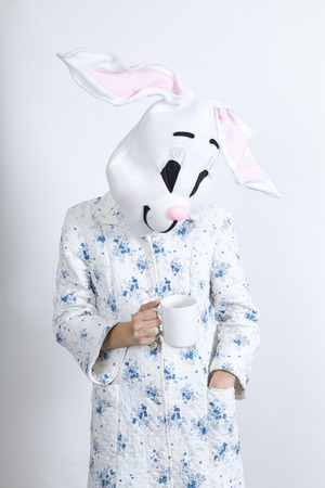 Rabbit difficult to wake in the morning Drinking a cup of coffee dressing-up clothes and conceptual parody Stock Photo