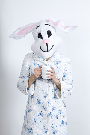 parody: Rabbit difficult to wake in the morning Warming himself with an hot cup of coffee dressing-up clothes and conceptual parody