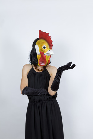 pretentious: Woman wearing a cock mask with an evening dress and evening gloves Stock Photo