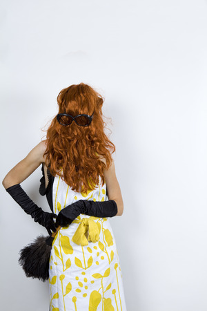 bashfulness: anonymous faceless housewife wearing an apron over an evening dress and evening gloves wig upside down, front face glasses on the wig Stock Photo