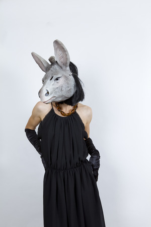bashfulness: Woman wearing a donkey mask with an evening dress and evening gloves