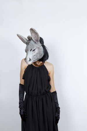 Woman wearing a donkey mask with an evening dress and evening gloves photo