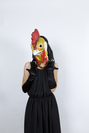 bashfulness: Woman wearing a cock mask with an evening dress and evening gloves Stock Photo