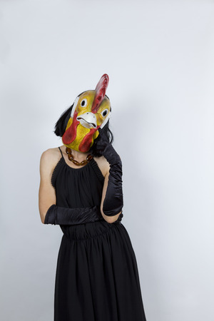 Woman wearing a cock mask with an evening dress and evening gloves Stock Photo