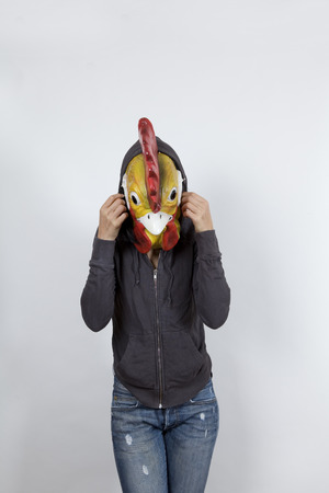 Woman wearing a cock mask and miming hip hop culture She is wearing a hoody and a jeans with holes