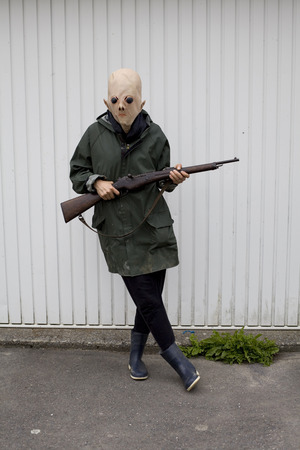 Colour photography. Woman wearing an alien mask hunting with shotgun in front of a garage door