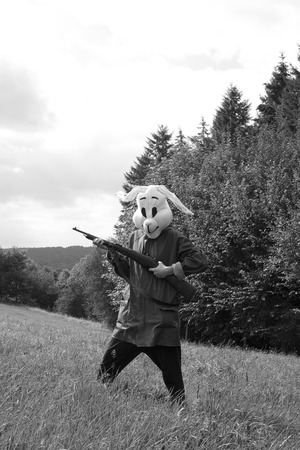 black and white photography. woman hunter wearing a rabbit mask hunting with shotgun in a forest Stock Photo