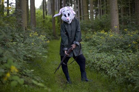 woman wearing a rabbit mask hunting with shotgun in a forest