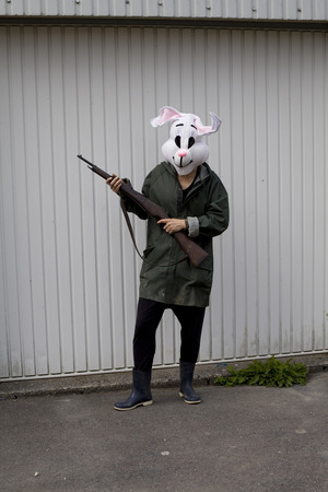 color photography: Color photography. Woman wearing a rabbit mask hunting with shotgun in front of a garage door