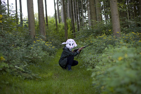 holding gun to head: woman wearing a rabbit mask hunting with shotgun in a forest