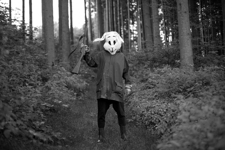 holding gun to head: black and white photography. woman hunter wearing a rabbit mask hunting with shotgun in a forest Stock Photo
