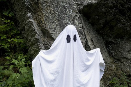 A spooky white ghost covered by a sheet with slits over the eyes standing in front of a rock.