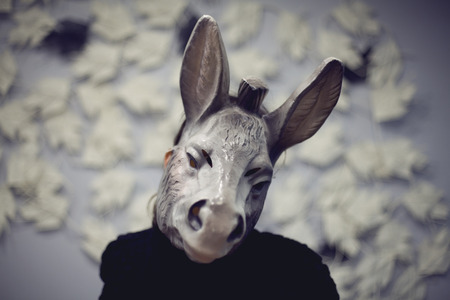 A woman wearing a donkey mask doing a selfie Blured color photography