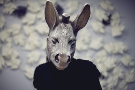 color photography: A woman wearing a donkey mask doing a selfie Blured color photography