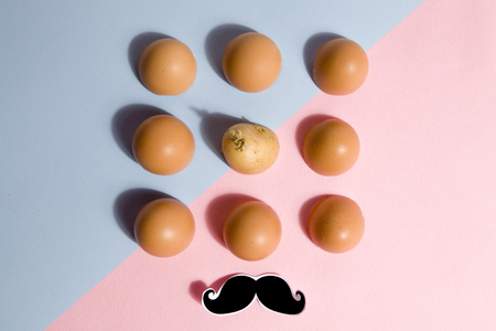 singularity: Eggshells lined up with a potato hidden in the batch blue and pink background with black shadow