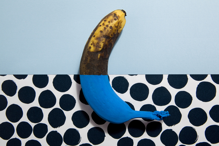 inverse: A half-painted banana blue Each half opposing the plain background and dots