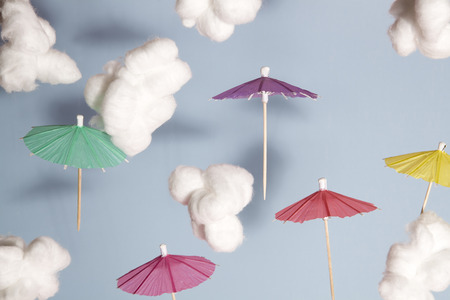 padding: Color cocktail umbrella flying in the air between cotton wool as cloud Blue background Stock Photo