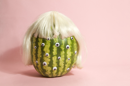 to metamorphose: Freak watermelon wearing a wig and crown on a pink background