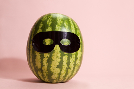 Superwatermelon wearing a black mask on a pink background