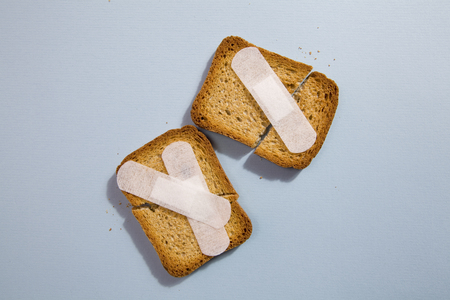 Repair a broken rusk with a plaster medical on a blue background