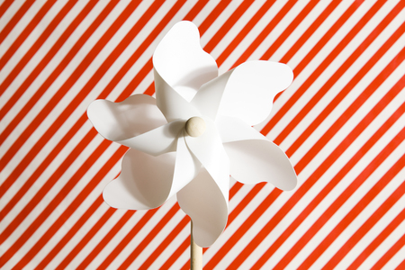 wind mill toy: A white pinwheel on a Striped red and white background