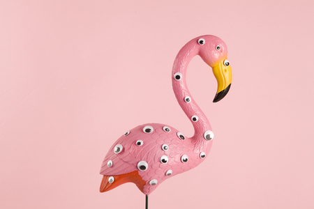 quirky and freak pink plastic flamingo on a pink background with numerous eyes gradient and tones on tones