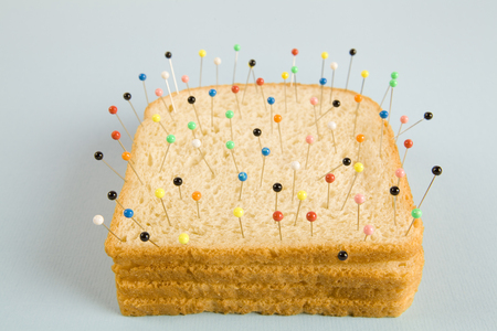 still life photography of a quirky soft bread stacked and used as a voodoo doll on a blue and minimal background Stock Photo