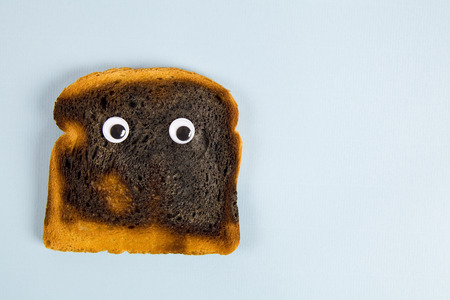a quirky burned soft bread with eyes doll Still life and minimal photography