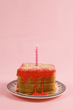 a quirky icing birthday bread covered with sprinkles and red coulis on pink background