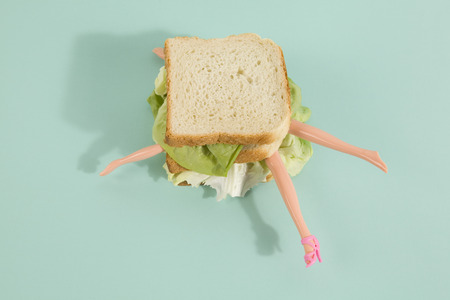 Parts of a dolls body in a sandwich with salad and soft bread on a minimal background color. pop fun and quirky cannibalism