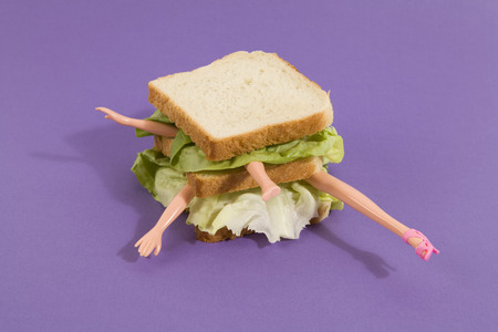 Parts of a doll's body in a sandwich with salad and soft bread on a minimal background color.pop fun and quirky cannibalism