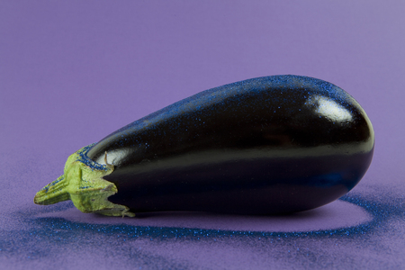 Pop minimal still life photography. Shiny eggplant with blue paillettes on a purple background using gradient colors and tones on tones