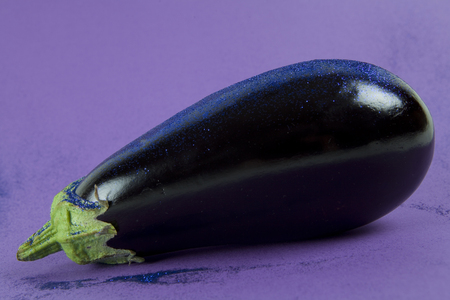 sequin: Pop minimal still life photography. Shiny eggplant with blue paillettes on a purple background using gradient colors and tones on tones