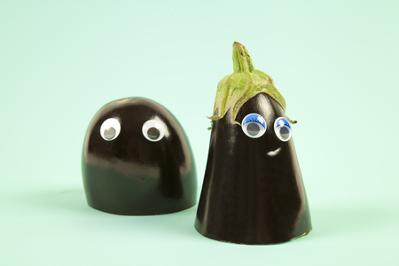 represents: Minimal still life photography.An aubergine cut in half. Each part, wearing dolls eyes represents a man and a woman. Dredge scene on a pop colored background