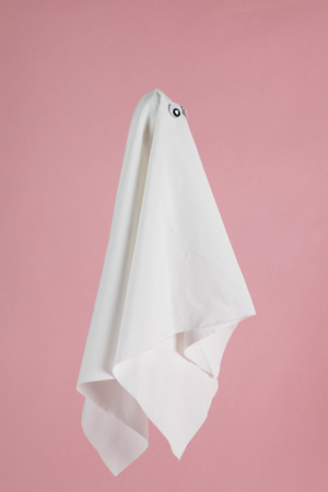 phantom: white sheet ghost with dolls eyes isolated on a pink background. Studio still life minimal photography