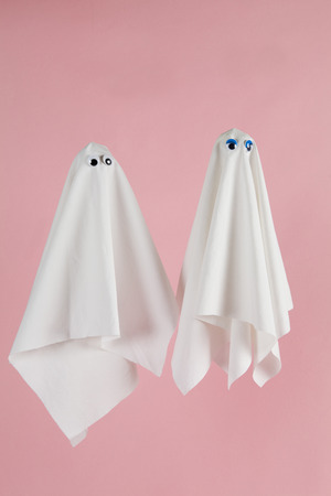 muneca vintage: Couple of white sheet ghost with dolls eyes isolated on a pink background. Minimal pop still life photography