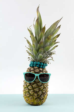 Playful pineapple wearing sunglasses and palm cocktail on a pop bi-color background turquoise and white like horizon. Minimal design still life photography Stock Photo