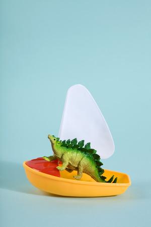 Un dinosaurio perdido en el mar en un barco de juguete como una metáfora del arca de Noé. Minimal Poetic still life photography Foto de archivo