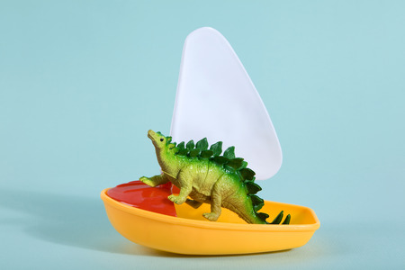 A dinosaur lost at sea on a toy boat like a noahs ark metaphor. Minimal Poetic still life photography Foto de archivo