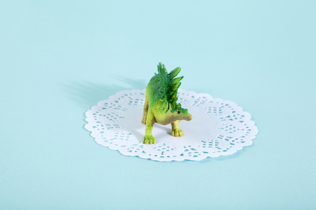 neon green: A dinosaur stegosaurus on a white lace paper doily with a vibrant turquoise background. Minimal offbeat still life photography