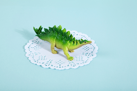 stegosaurus: A dinosaur stegosaurus on a white lace paper doily with a vibrant turquoise background. Minimal offbeat still life photography