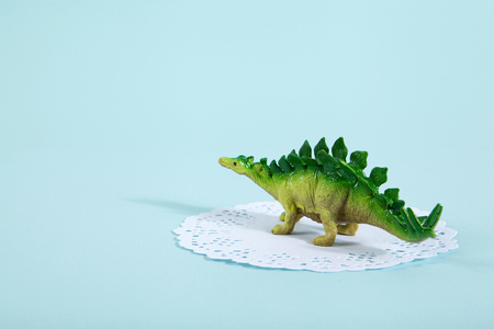 A dinosaur stegosaurus on a white lace paper doily with a vibrant turquoise background. Minimal offbeat still life photography