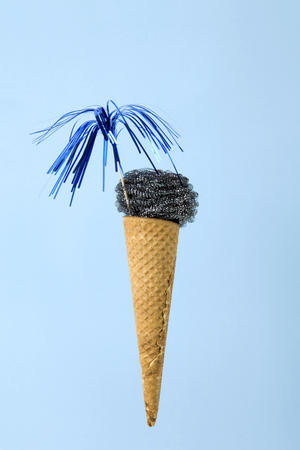 An ice cream cone whose scoop is replaced by a metallic scouring pad sponge. Photographic composition funny and offbeat. Fun, minimal and surreal color still life photography Banco de Imagens