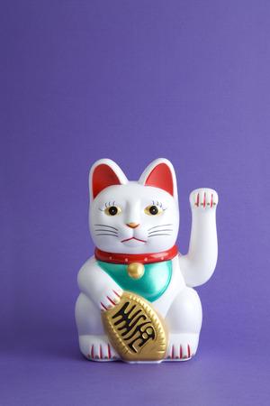 a Maneki-neko plastic cat, Symbolizing luck and wealth, on a pop and colorful background.Minimal color still life photography Standard-Bild